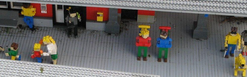 Lego figures standing on a station platform
